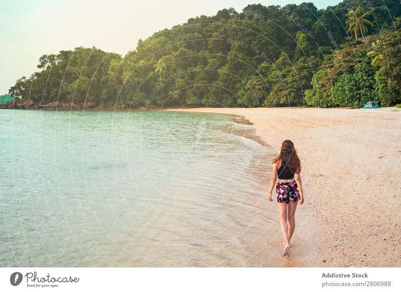 Frau, die am Sandufer in der Nähe des Wassers spazieren geht. Strand Meer laufen Jamaika Wald