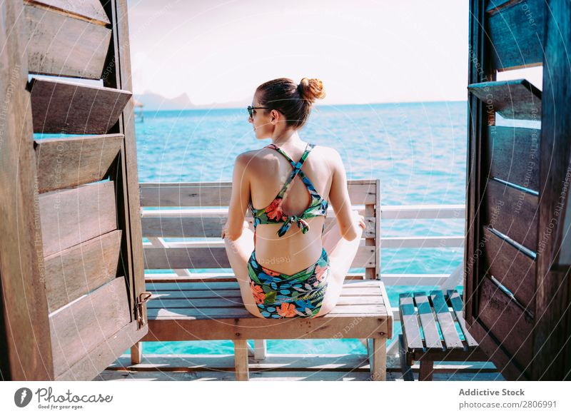 Frau im Bikini sitzt auf einer Bank in der Nähe des Wassers. Meer Jamaika Sonnenbrille Badeanzug Sitz blau tropisch exotisch sitzen Accessoire Sommer dünn Dame