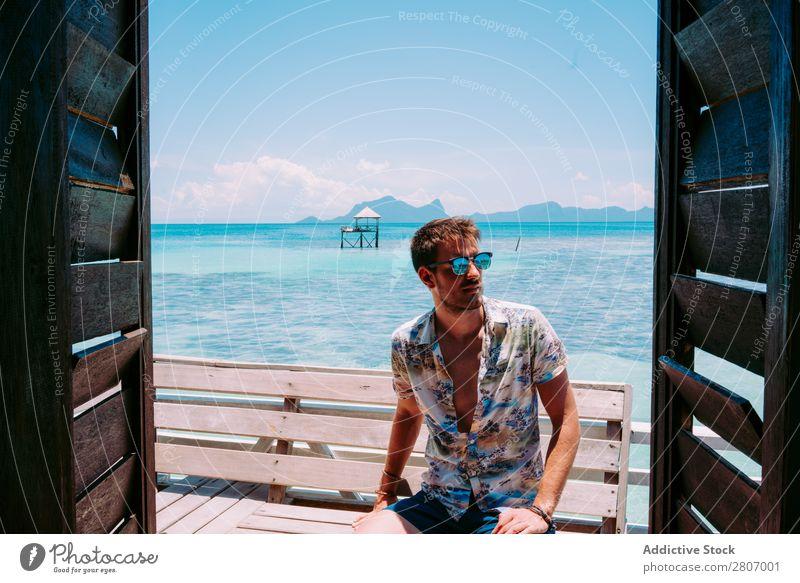 Mann mit Sonnenbrille sitzt auf einer Bank in der Nähe des Wassers. Meer Jamaika Sitz blau tropisch exotisch sitzen Jugendliche aussruhen Accessoire Sommer Typ