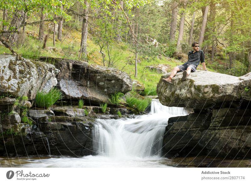 Junger Mann ruht sich nach dem Abenteuer am Wasserfall aus. Natur Sommer Ferien & Urlaub & Reisen genießend Gesundheit Körper Entwurf grün frisch gutaussehend