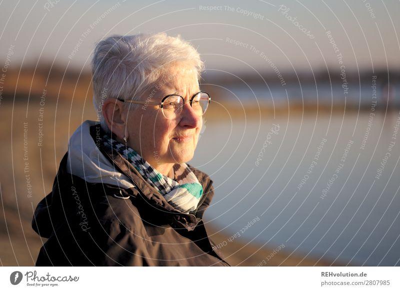 Seniorin im Abendlicht blickt in die Ferne See Wasser weite nachdenklich Brille Jacke Zukunft sorgen Natur Umwelt kritisch Mensch ruhig stille Himmel