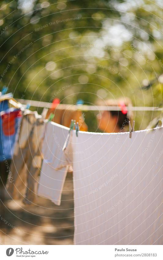 Frau trockene Kleidung im Freien Frühling Wäscheleine Lifestyle Kleiderhaken Wäscherei trocknen Haushalt Waschtag Farbfoto Außenaufnahme Bekleidung aufhängen