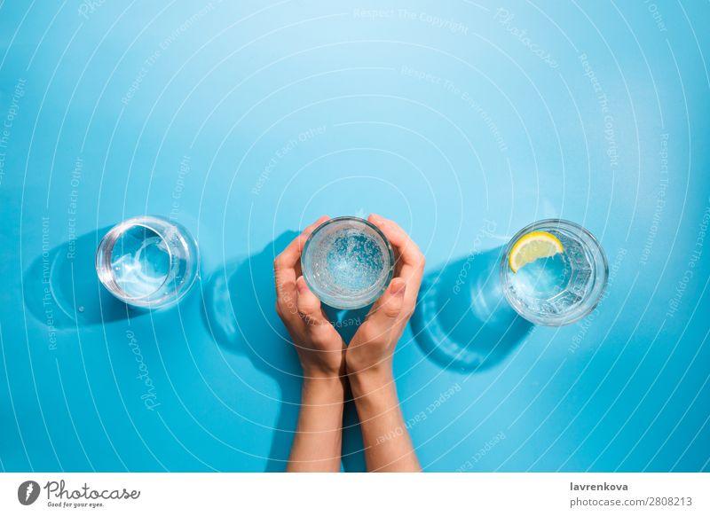 Die Hände der Frau halten eine Tasse sauberes Mineralwasser. frisch Sauberkeit Flasche Objektfotografie Getränk kalt Sommer Becher Glas Verschiedenheit