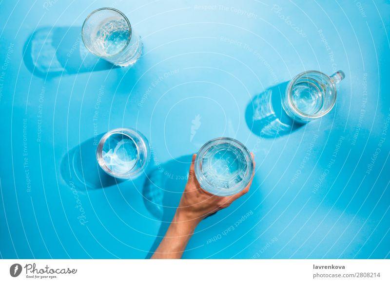 Die Hände der Frau halten eine Tasse sauberes Mineralwasser. Reflexion & Spiegelung Gesundheit frisch Coolness rein blau hell durchsichtig Urelemente Tropfen