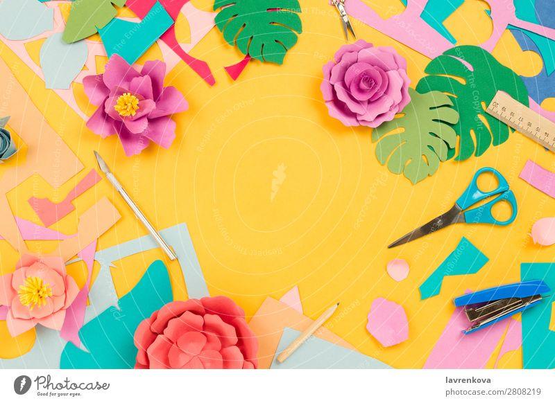Papierbedarf und Papierblumen auf gelbem Hintergrund blau Farbe rosa Feiertag Schreibstift Teppichmesser Heftklammerer Lineal Schere geschnitten Gänseblümchen