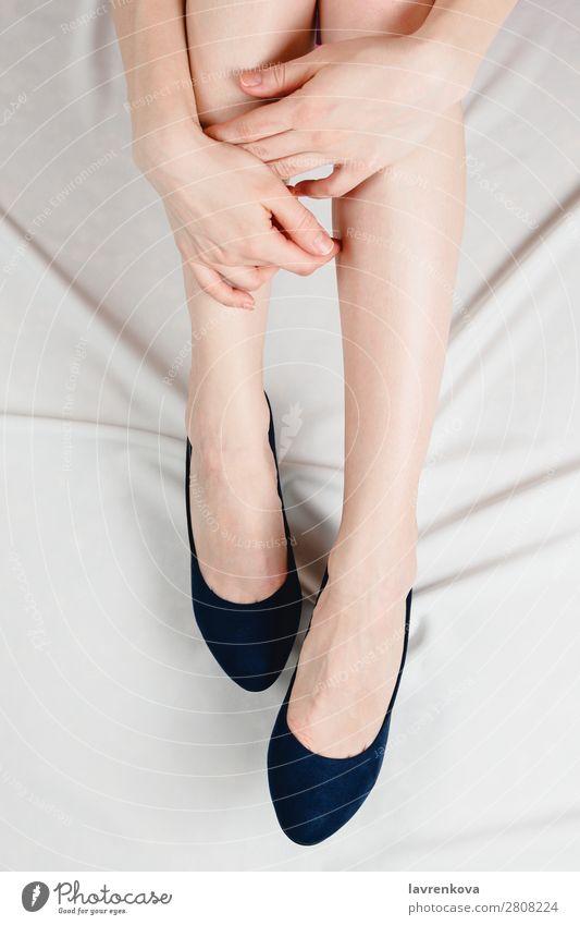 Oben Schuss einer weißen Frau, die ihre Beine in Schuhen hält. Körper gesichtslos Fußknöchel Damenschuhe Hand Mode Mensch Erwachsene Haut Junge Frau Gesundheit