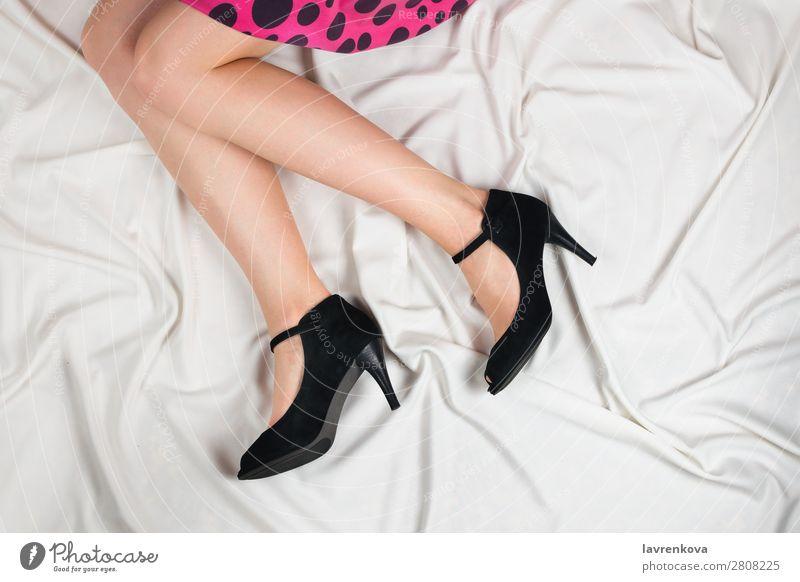 Oben ein Schuss von weißen Frauenbeinen in hochhackigen Schuhen. Lifestyle Kaukasier Bettwäsche Bettlaken Ankleidezimmer Kleid Körper gesichtslos Fußknöchel
