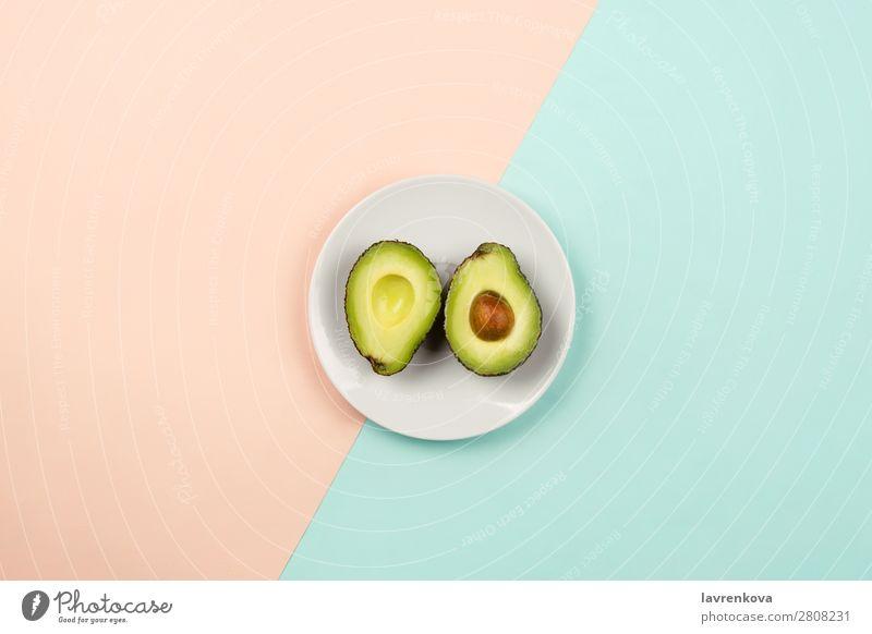 Avocado auf weißem Teller auf pastellfarbenem Hintergrund schneiden Scheibe natürlich roh frisch grün geschnitten reif organisch Ernährung