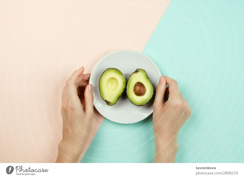 Avocado auf weißem Teller und Frauenhänden schneiden. Vegetarische Ernährung Vegane Ernährung Frucht Essen flache Verlegung Zutaten Diät Gesundheit