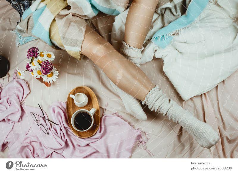 Weißgebräunte Frau in weißen Socken, die in ihrem Bett sitzt. gemütlich Winter Herbst flache Verlegung Hygge Erwachsene Einsamkeit schön Bettwäsche Decke