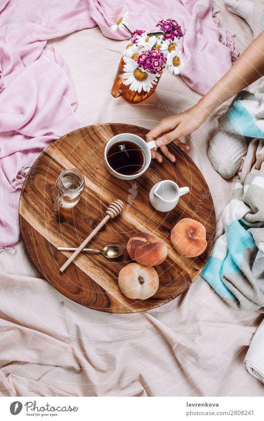 Gemütliches Flachbett aus Holztablett mit Tasse Kaffee, Pfirsichen, Kaffeesahne und Sahne. Becher Flachlegung flache Verlegung Schlafzimmer Frühstück Espresso