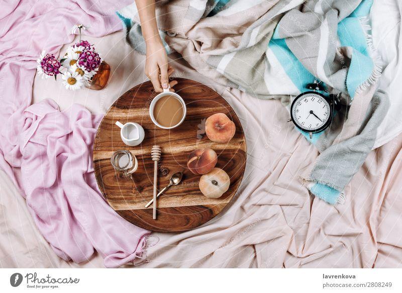 Gemütliches Flachbett aus Holztablett mit Tasse Kaffee, Pfirsichen, Kaffeesahne und Sahne. Wecker Morgen Becher Flachlegung flache Verlegung Schlafzimmer