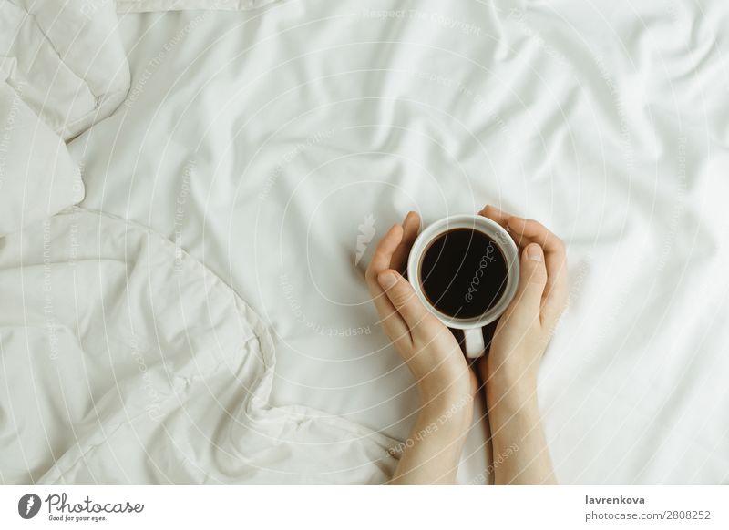 Frauenhände halten Tasse Kaffee im Bett auf weißen Laken. Winter Herbst Getränk flache Verlegung Bettlaken Lifestyle weich Becher Hand Wärme Geborgenheit