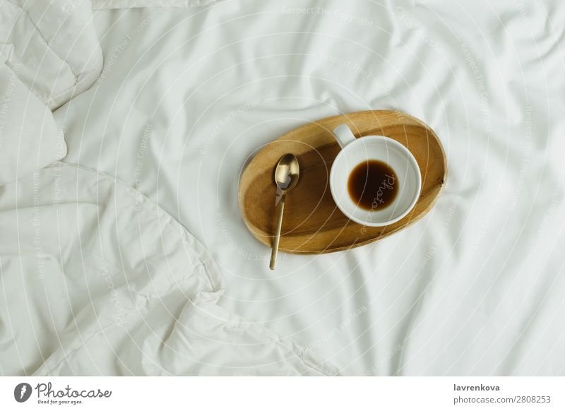 Tasse Kaffee und Löffel auf Holztablett im Bett auf weißen Laken Tablett Schlafzimmer Espresso Gesundheit Gesunde Ernährung Feiertag Tee Getränk schwarz heiß