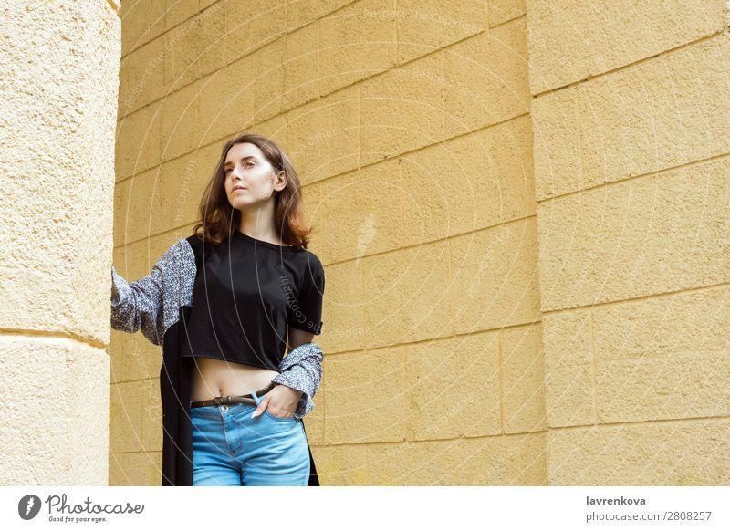 Porträt einer jungen erwachsenen Frau vor der gelben Wand Erwachsene attraktiv schön Freizeitbekleidung Kaukasier Großstadt Gesicht Mode Junge Frau Behaarung