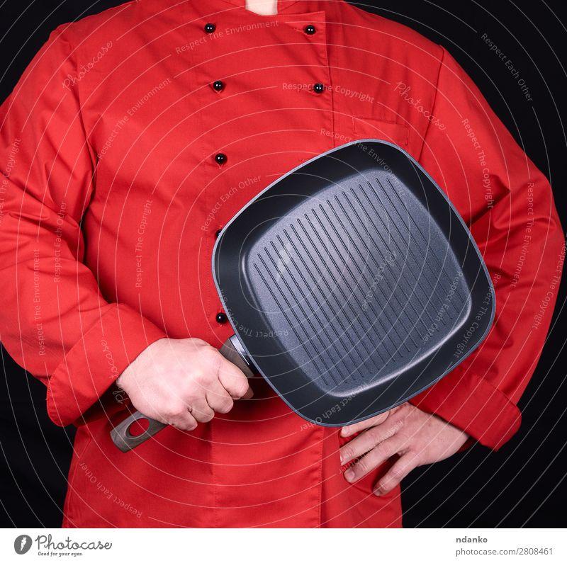 Koch mit einer leeren quadratischen schwarzen Bratpfanne Pfanne Küche Restaurant Mensch Mann Erwachsene Hand Bekleidung rot Gußeisen Kaukasier Küchenchef