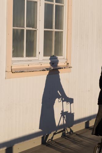 Schatten von einer Dame mit Rollator Mensch feminin Weiblicher Senior Frau 1 Fassade Fenster Fußgänger Bewegung laufen alt Krankheit Vertrauen Gehhilfe
