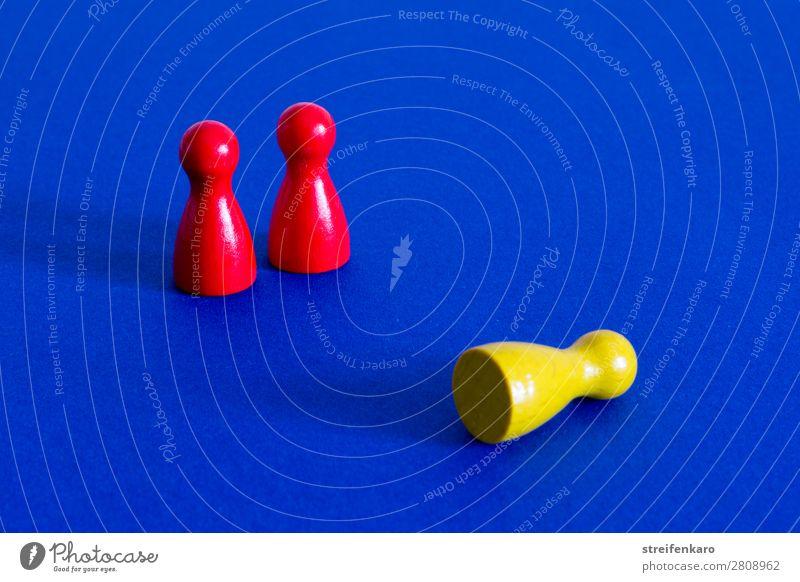 Eine gelbe Spielfigur liegt vor zwei stehenden roten Spielfiguren auf blauem Untergrund Wirtschaft Business Unternehmen Erfolg Team Spielzeug Holz fallen Jagd
