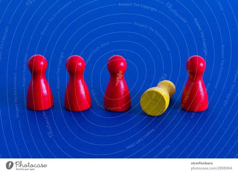 Gelbe Spielfigur liegt in einer Reihe von roten Spielfiguren auf blauem Untergrund Spielen Menschengruppe Holz Zeichen fallen liegen stehen Zusammensein gelb