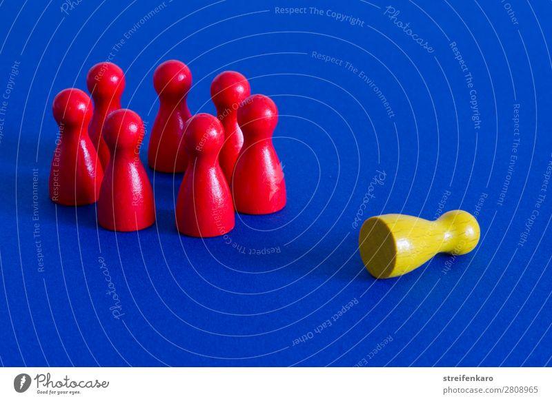 Eine gelbe Spielfigur liegt außerhalb eines Kreises aus roten Spielfiguren auf blauem Untergrund Menschengruppe Spielzeug Holz wählen sprechen liegen stehen