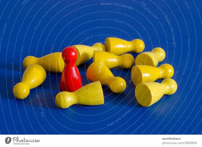 Eine rote Spielfigur steht inmitten von gelben liegenden Spielfiguren auf blauem Untergrund Menschengruppe Spielzeug Holz fallen kämpfen stehen Aggression