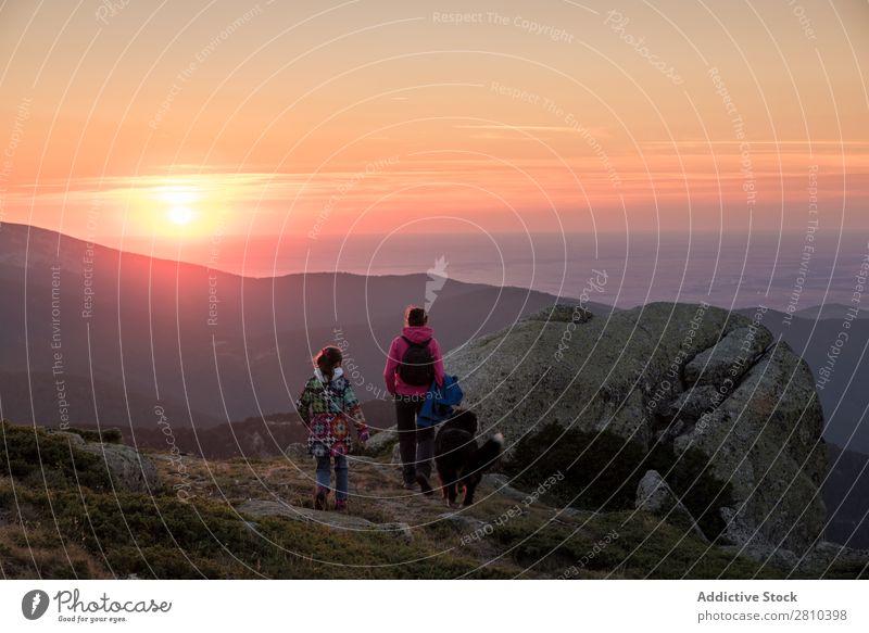 Mutter und Tochter beobachten den Sonnenuntergang auf dem Gipfel des Berges. wandern Ferien & Urlaub & Reisen Kind Frau Ausflug Berge u. Gebirge Sonnenaufgang