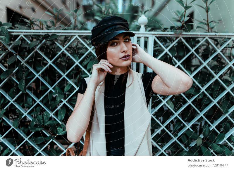 Ziemlich stylische Frau, die eine Kappe aufsetzt. Stil Jugendliche Straße schön Mütze anmachend Zaun Großstadt Mode hübsch attraktiv Model Mensch