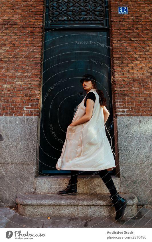 Stilvolle Frau, die zum Haus geht. Jugendliche Straße schön Mütze Veranda Backstein laufen Großstadt Mode hübsch attraktiv Model Mensch Beautyfotografie Porträt