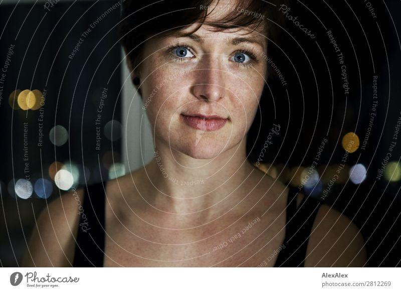 Portrait einer jungen Frau mit Sommersprossen elegant Freude schön Wohlgefühl Raum Fenster Stadtlicht Junge Frau Jugendliche Erwachsene Gesicht 18-30 Jahre Top