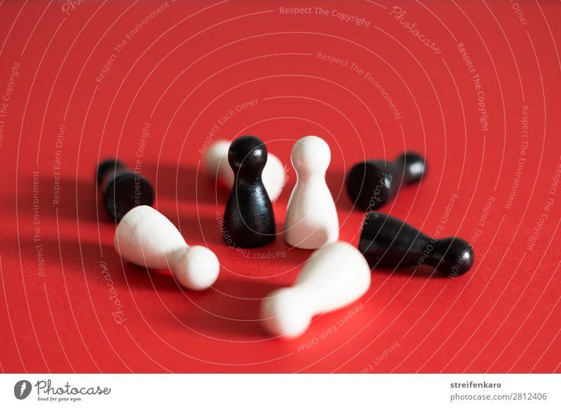 Eine schwarze und eine weiße Spielfigur stehen sich gegenüber, umgeben von liegenden schwarzen und weißen Figuren, auf rotem Untergrund Spielen Wirtschaft