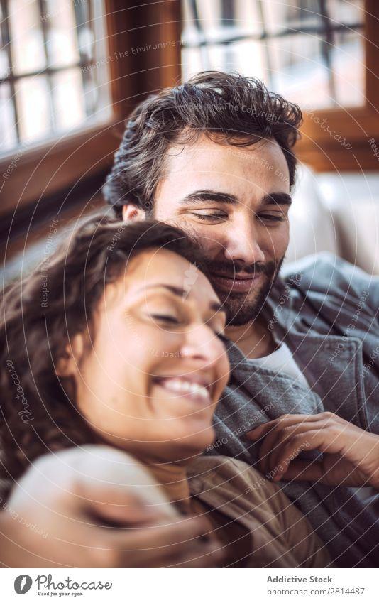Junges Paar auf dem Sofa in der Liebe Liege heimwärts Erholung Lächeln Innenarchitektur Geborgenheit Fürsorge Wohnzimmer sitzen Fröhlichkeit umarmend