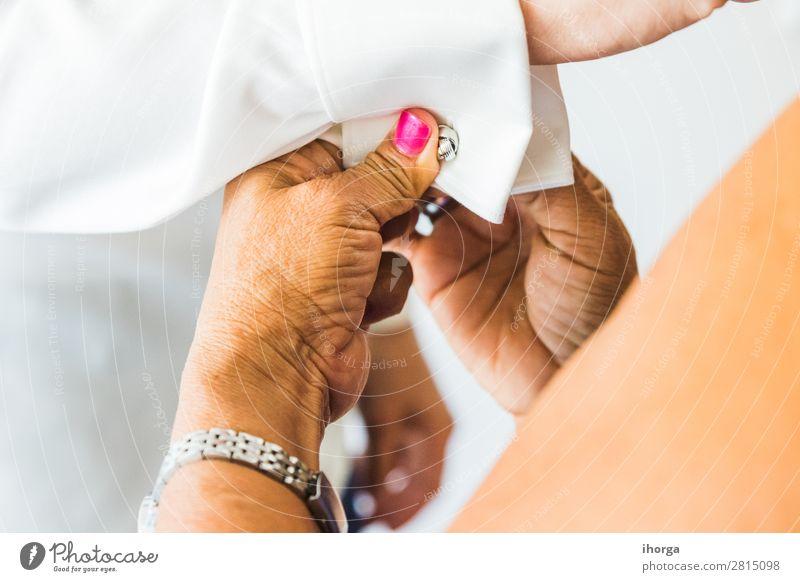 Ein Bräutigam, der an seinem Hochzeitstag Manschettenknöpfe anlegt. Reichtum elegant Stil Büro Business Mensch maskulin Mann Erwachsene Hand 1 Mode Bekleidung