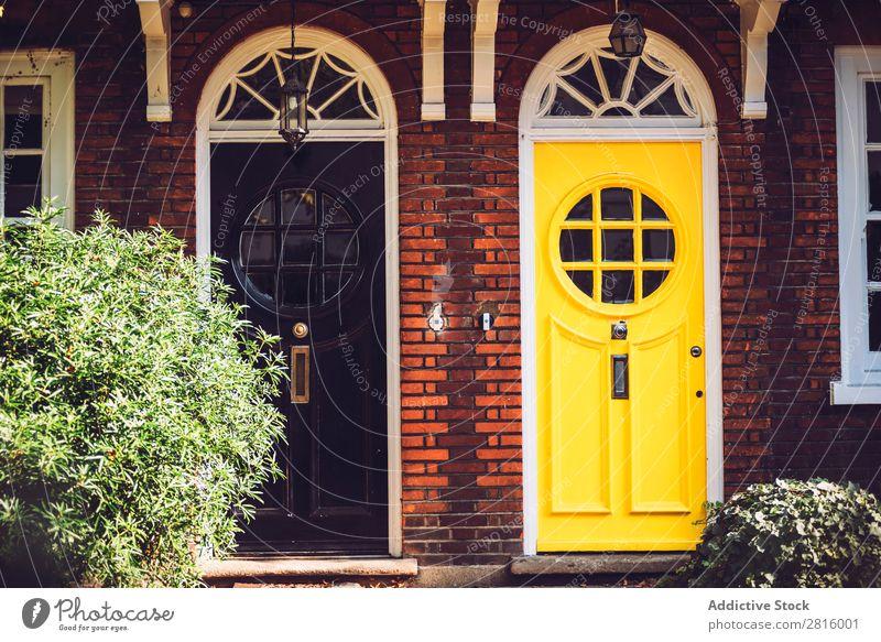 Helle Vintage-Türen. altehrwürdig London hell schwarz gelb gestylt Eingangstür rund Fenster Glas Holz Farbe mehrfarbig Außenaufnahme Außenseite Vorderansicht