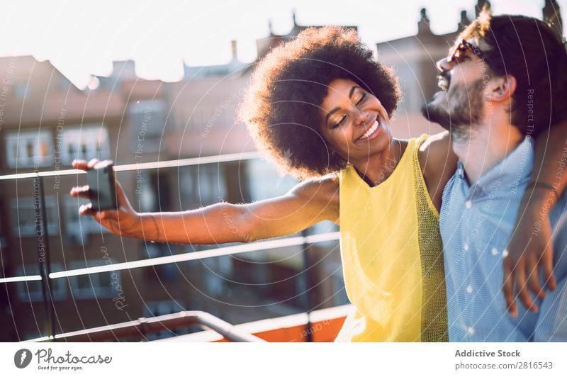 Junges multikulturelles Paar, das Selfie nimmt und verliebt auf dem Dach lacht. anhänglich Afrikanisch schön Freund Kaukasier Solarzelle Datierung