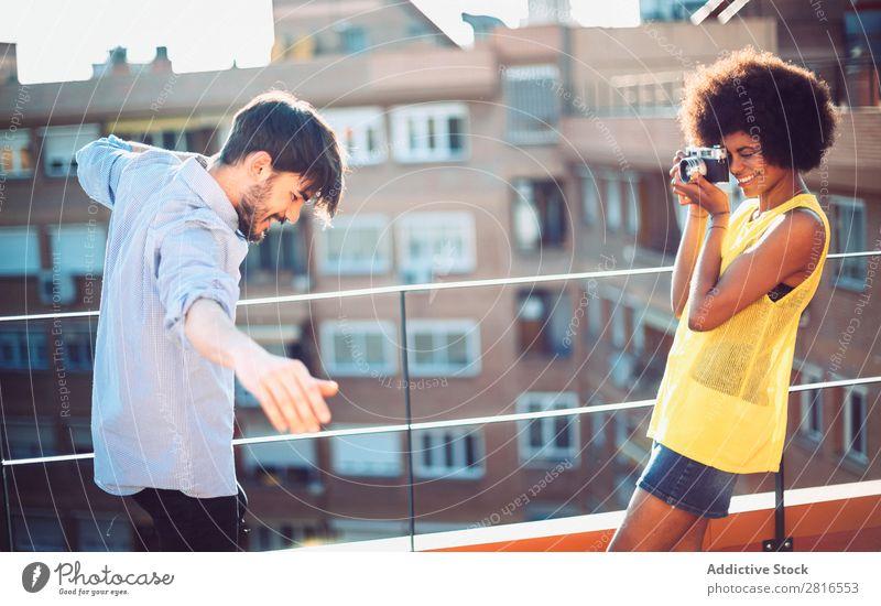 Interrassisches junges Paar, das sich gegenseitig fotografiert und Spaß hat. Jugendliche gutaussehend multikulturell interrassisch Sommer Außenaufnahme lässig