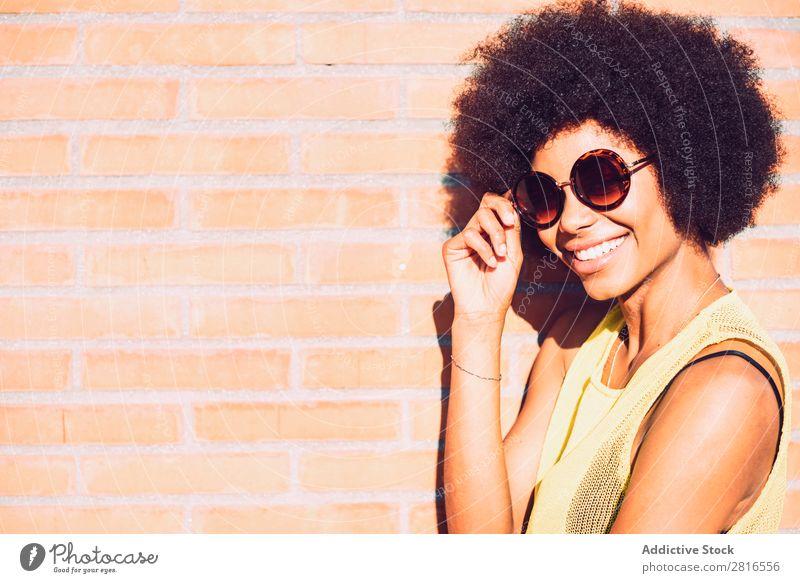 Junge schöne afroamerikanische Frau, die posiert und lächelt, während sie an der Ziegelwand steht. Afrikanisch Amerikaner charmant Backstein Model Hand