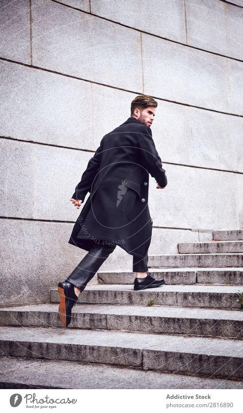 Junger, gutaussehender, trendiger Mann mit Mantel, der auf der Treppe posiert. Erwachsene attraktiv Vollbart bärtig lässig Kaukasier Coolness niedlich tief