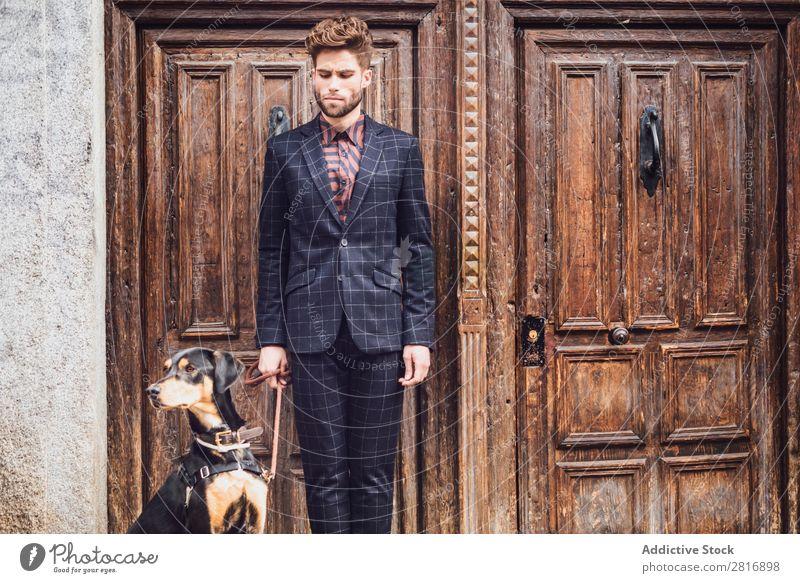 Schöner eleganter junger Modemann im trendigen Kostümanzug mit Hund, alter Holztürhintergrund Anzug Mann Herr modisch Bekleidung Stil Model Hemd Hand lässig
