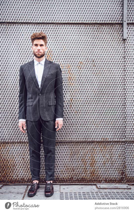 Schöner eleganter junger Modemann im trendigen Kostümanzug, Metallzaun Hintergrund Anzug Mann Herr modisch Bekleidung Stil Model Hemd Hand lässig modern