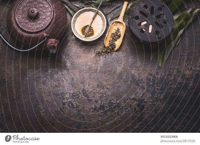 Traditioneller asiatischer Grünteehintergrund mit schwarzer Eisenteekanne, Kerze und Honig auf dunklem, rustikalem Hintergrund mit Kopierfeld, Draufsicht