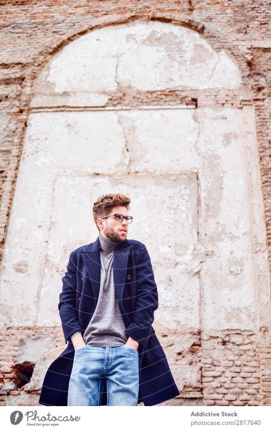 Junger, gutaussehender, trendiger Mann mit Mantel, der mit einem alten Wandhintergrund posiert. Erwachsene attraktiv Vollbart bärtig lässig Kaukasier Coolness