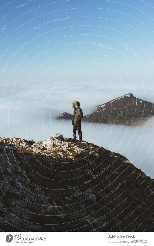 Mann auf felsigem Felsen in Wolken Börde Berge u. Gebirge Aussicht Höhe Natur Gipfel