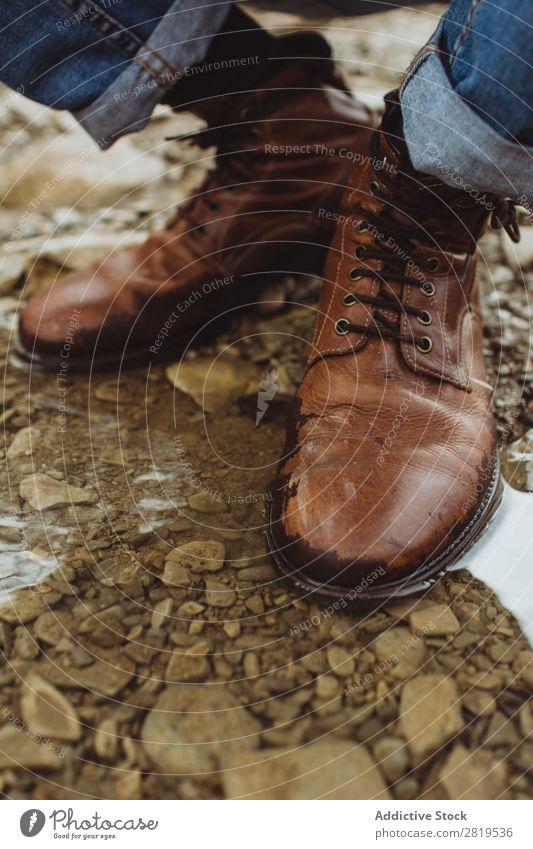 Beine in Lederstiefeln in der Pfütze Stiefel Natur Wanderer braun Stil wandern Abenteuer Stein Kieselsteine Trekking Aktion Jeansstoff Jeanshose Fuß laufen