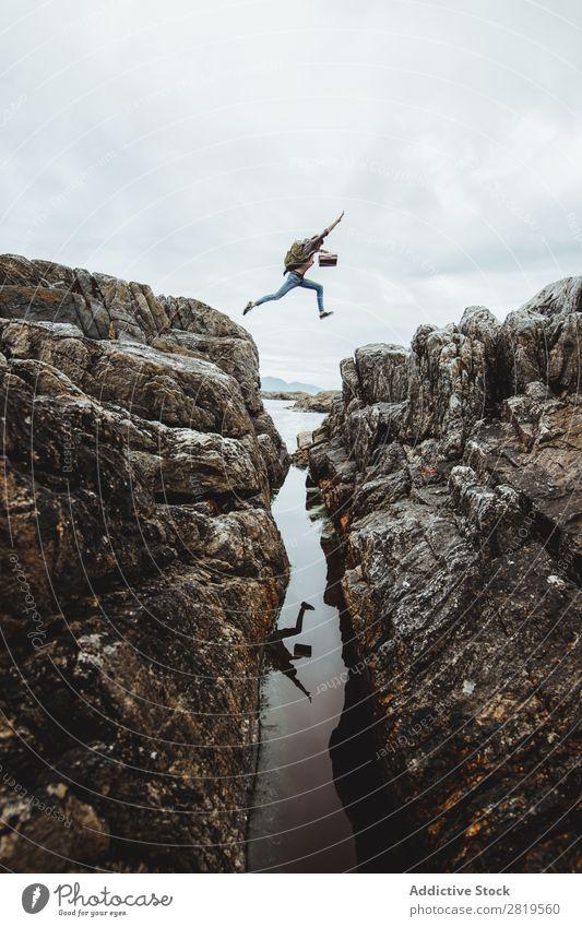 Tourist beim Springen über die Schlucht Berge u. Gebirge springen Ferien & Urlaub & Reisen Natur wandern Landschaft Felsen Tourismus Fluss Abenteuer Tal