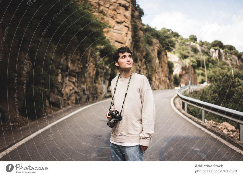 Mann mit Kamera, der auf einer Landstraße unterwegs ist. Fotokamera Landschaft Mensch attraktiv gutaussehend Freizeit & Hobby Ausflug Tourist lässig Natur