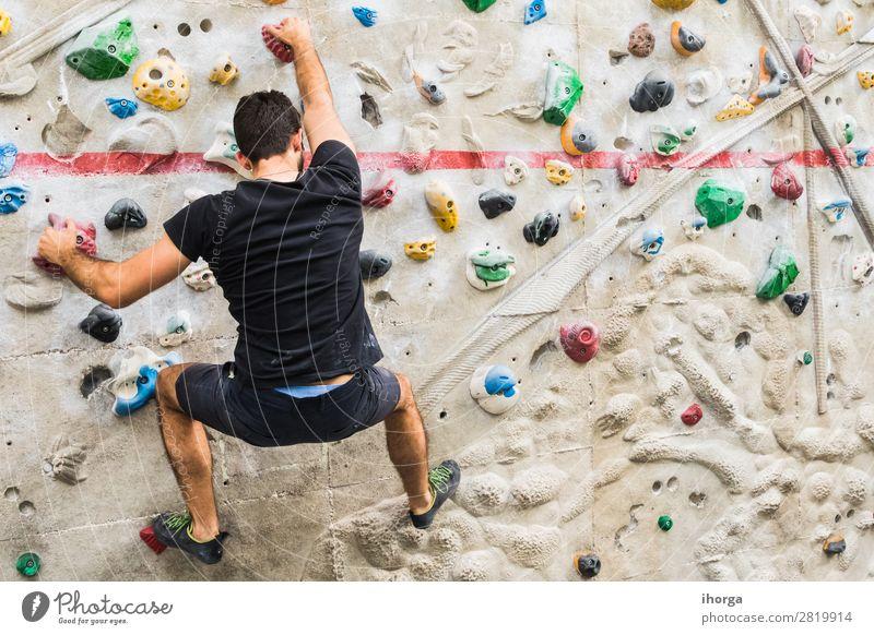 Mann übt Klettern an einer künstlichen Wand in Innenräumen. Lifestyle Freude Freizeit & Hobby Sport Bergsteigen Mensch Junger Mann Jugendliche Erwachsene 1