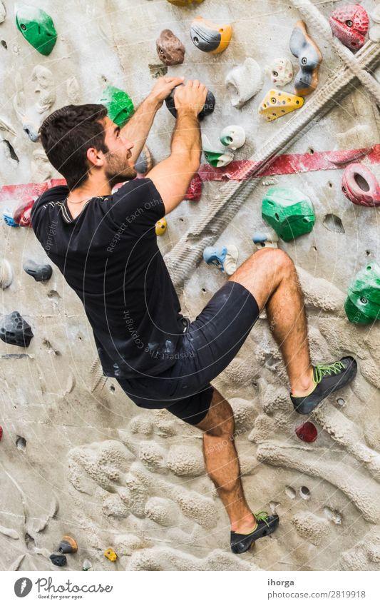Mann übt Klettern an einer künstlichen Wand in Innenräumen. Lifestyle Freude Freizeit & Hobby Sport Bergsteigen maskulin Erwachsene Hand Fuß 1 Mensch