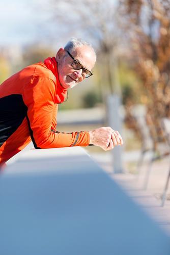 Senior-Läufer mit Sportbekleidung, die sich an einen Holzzaun lehnt. Lifestyle Erholung Joggen Telefon Mensch maskulin Mann Erwachsene Männlicher Senior 1