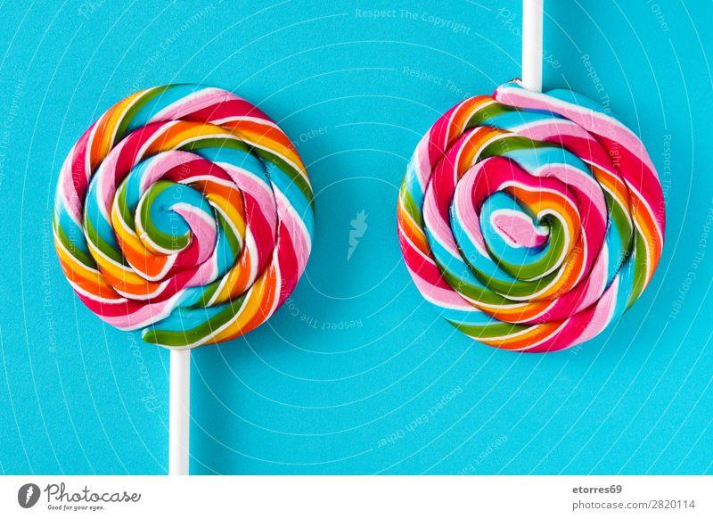 Bunte Lollis auf blauem Hintergrund. Draufsicht. Lollipop Farbe mehrfarbig Zucker Süßwaren Bonbon süß geschmackvoll Hintergrund neutral Hintergrundbild