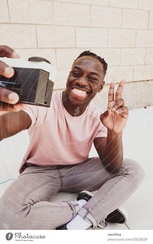 Junger Mann hält eine alte analoge Kamera. Lifestyle Stil Freude Haare & Frisuren Gesicht Freizeit & Hobby Fotokamera Technik & Technologie